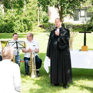 Pfarrer mit Musikern neben Altar auf grüner Wiese