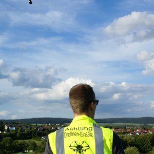 Drohnenpilot Stefan Vones, über ihm am leicht bewölkten Himmel eine Drohne